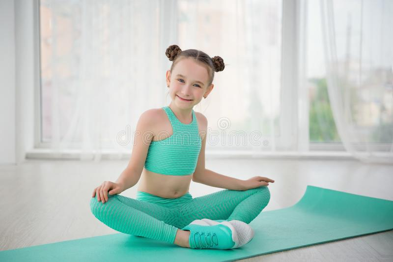 Little sporty girl gymnast in sportswear doing exercises on a mat indoor. Happy sporty girl gymnast in sportswear doing exercises on a mat indoor royalty free stock photo