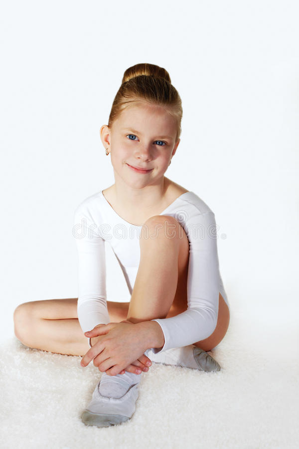 Little sporty girl sitting on the white carpet. royalty free stock photo