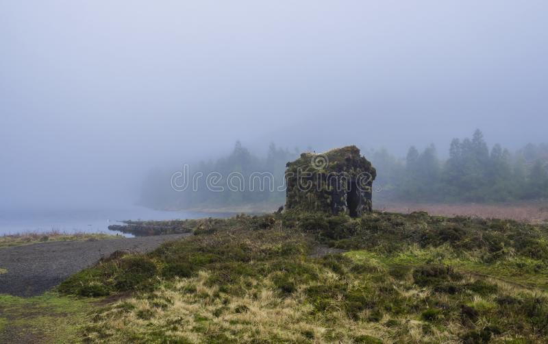 Little stone hut covered by moss at the shallow banks of lake Lagoa Rasa surrounded by green forest lost in mist. Mysterious moody day, the island of Sao royalty free stock photography