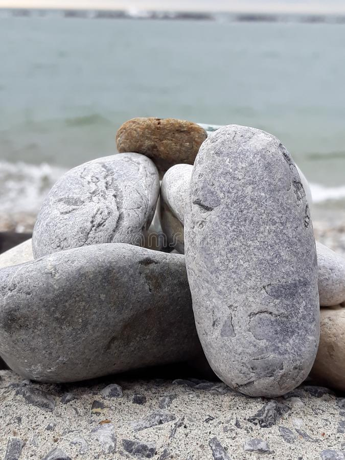 The little stones on a big rock at a afternoon at the beach. royalty free stock image