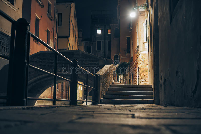 Little street and bridge at night in Venice, Italy stock images