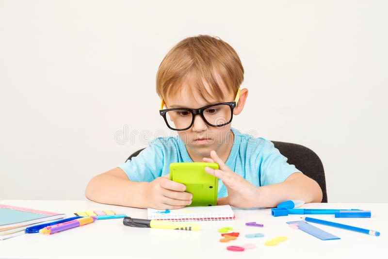 Little student boy counts something with calculator. Child doing homework at home. Preschool boy doing math exercise learning. Addition and counting. Education royalty free stock photos