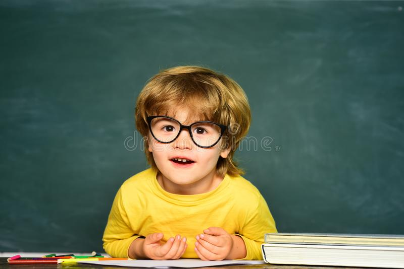 Little student boy happy with an excellent mark. Cute little preschool kid boy in a classroom. Cute boy with happy face. Expression near desk with school royalty free stock photos