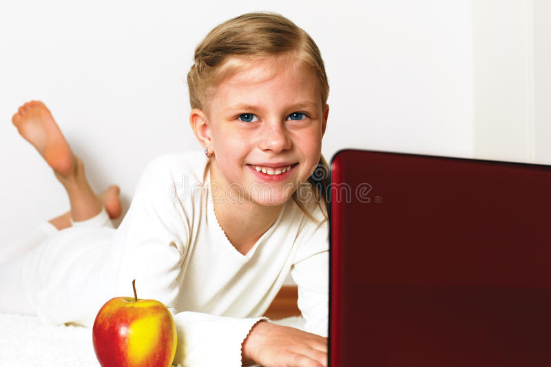Little student girl with laptop pc at home stock images