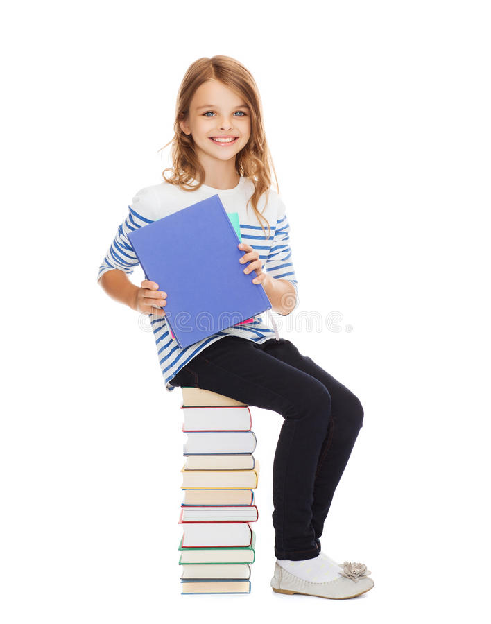 Little student girl sitting on stack of books royalty free stock photo