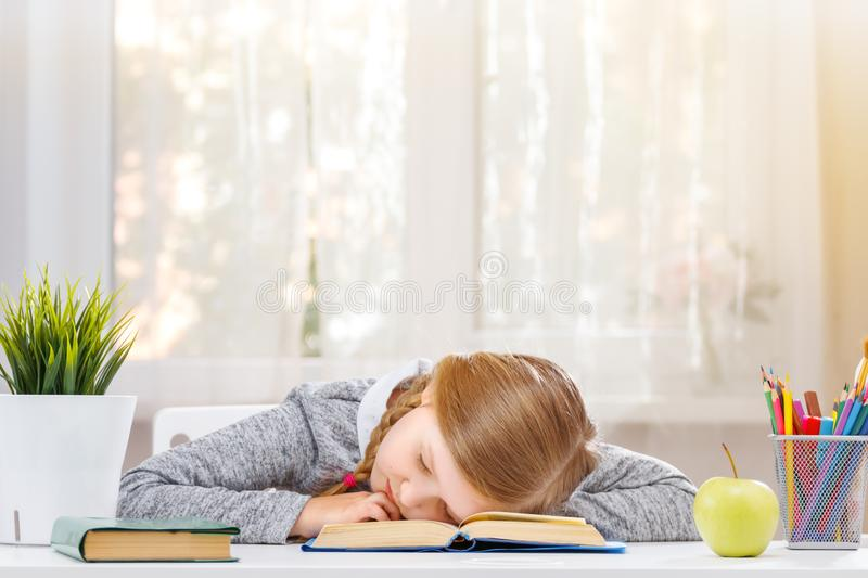 Little student girl sitting at the table, fell asleep at the books. The concept of education and school stock image