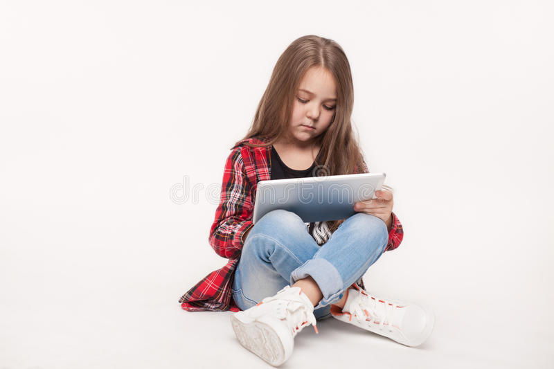 Little student girl with tablet pc doing homework stock images