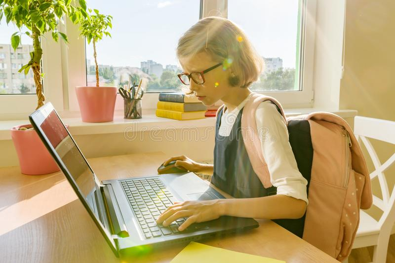 Little student girl of 8 years old in school uniform with a backpack uses laptop. School, education, knowledge and children. stock photo