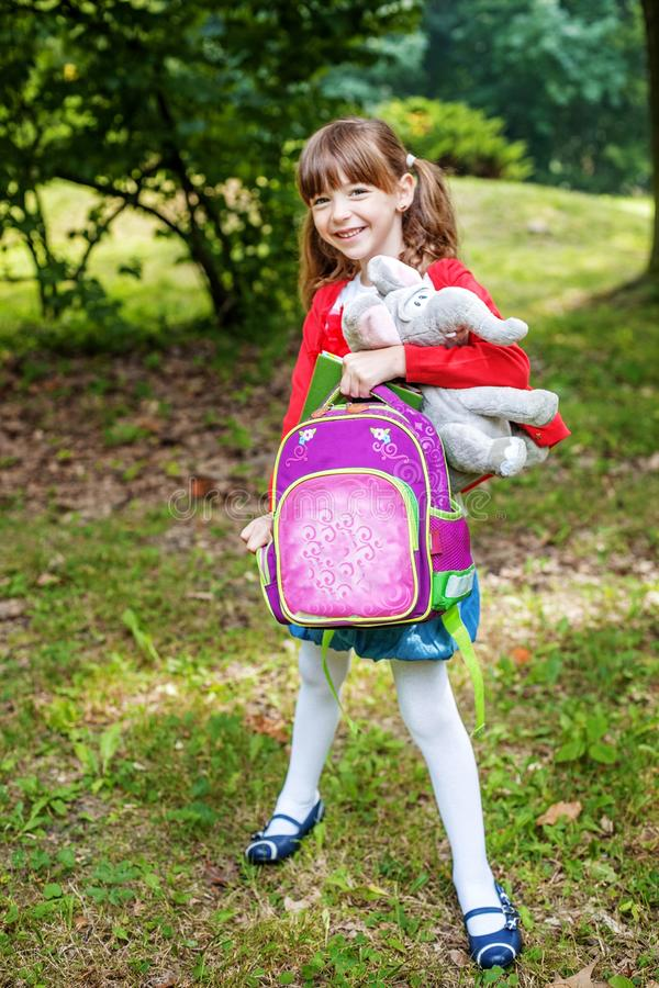 Little student leaves the school with a backpack. Beautiful chi royalty free stock images