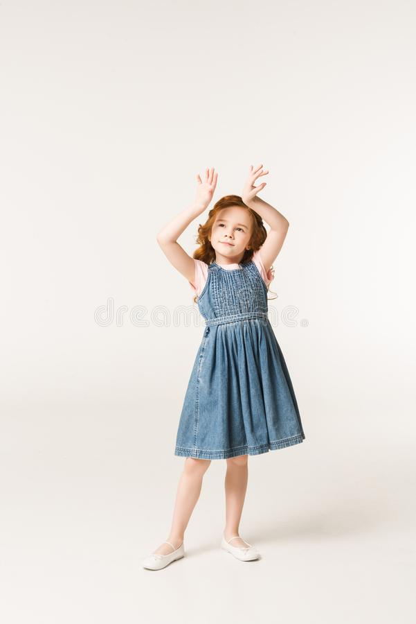 Little stylish child with arms up. Isolated on white stock images