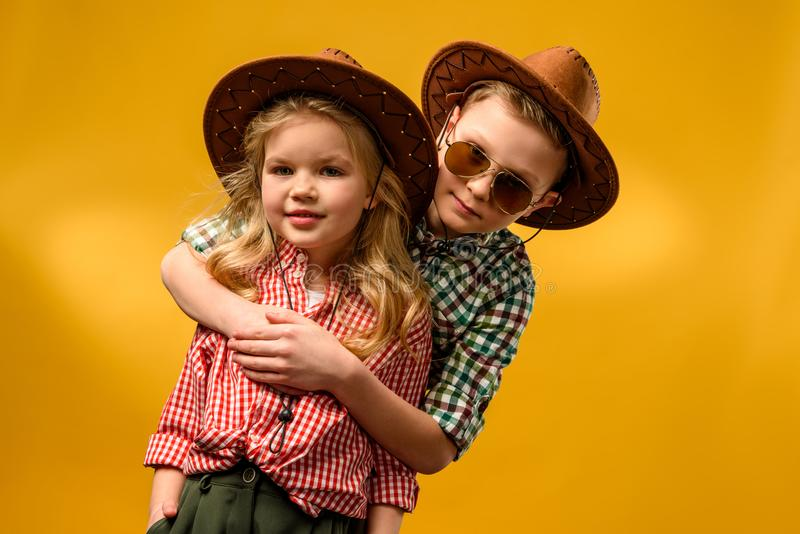 little stylish cowboy and cowgirl in hats hugging royalty free stock photo