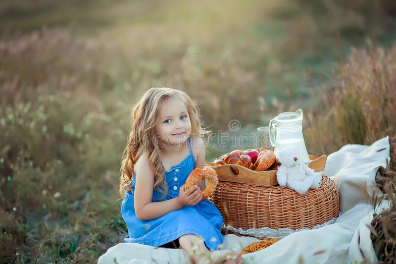 Little stylish kid wearing trendy checked shirt and jeans is having fun on the picnic. He is drinking yogurt and has stock images