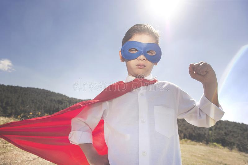 Superhero kid. Success concept. Vintage filtered image with selective focus royalty free stock image