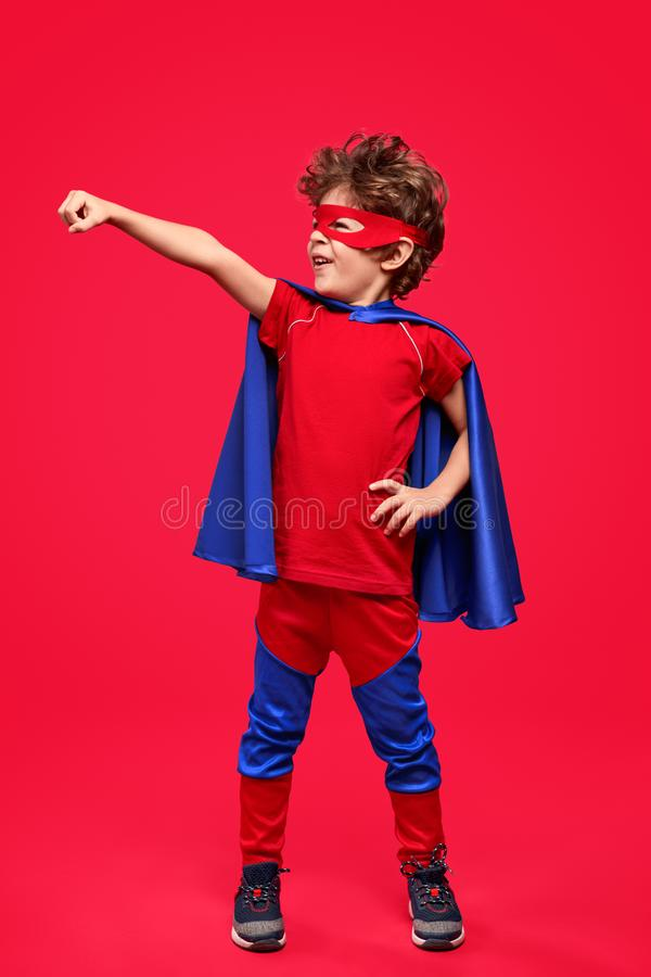Little superhero in courageous pose royalty free stock photography