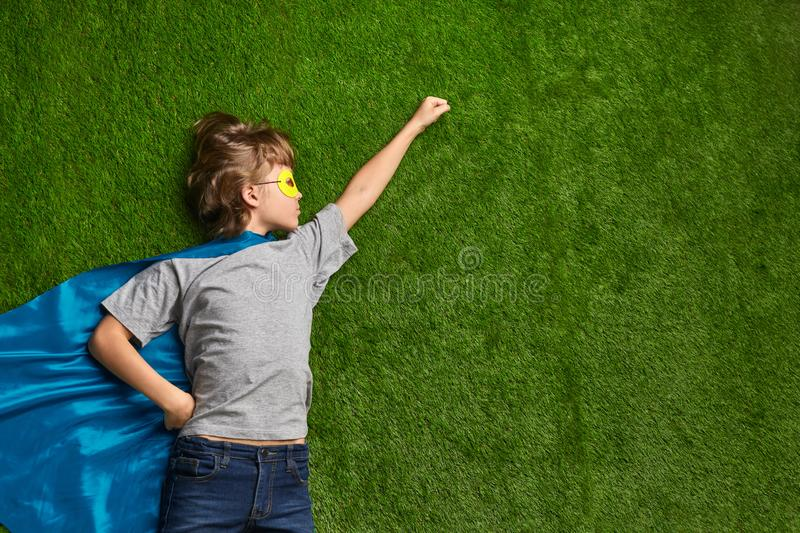 Little superhero flying against lawn. Little boy in superhero mask and cape lying in flying heroic pose against green grass royalty free stock photography