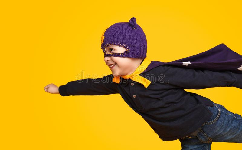 Little superhero flying on yellow background. Side view of cute little boy in superhero mask and cape smiling and flying on bright yellow background royalty free stock images