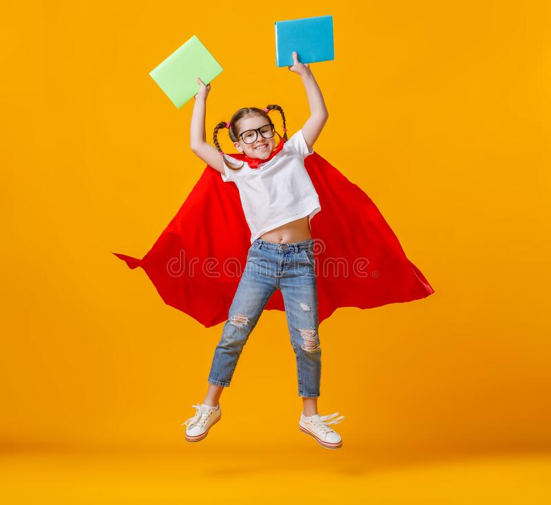 Little superhero jumping with notebooks royalty free stock image
