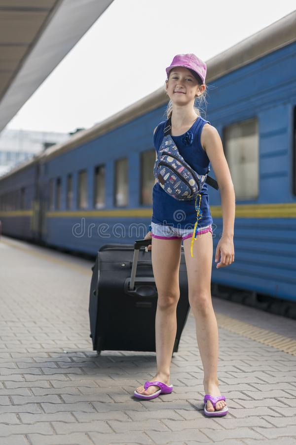 little sweet girl with a big suitcase on a deserted railway platform. girl pulling a large suitcase on the platform. vertical royalty free stock image