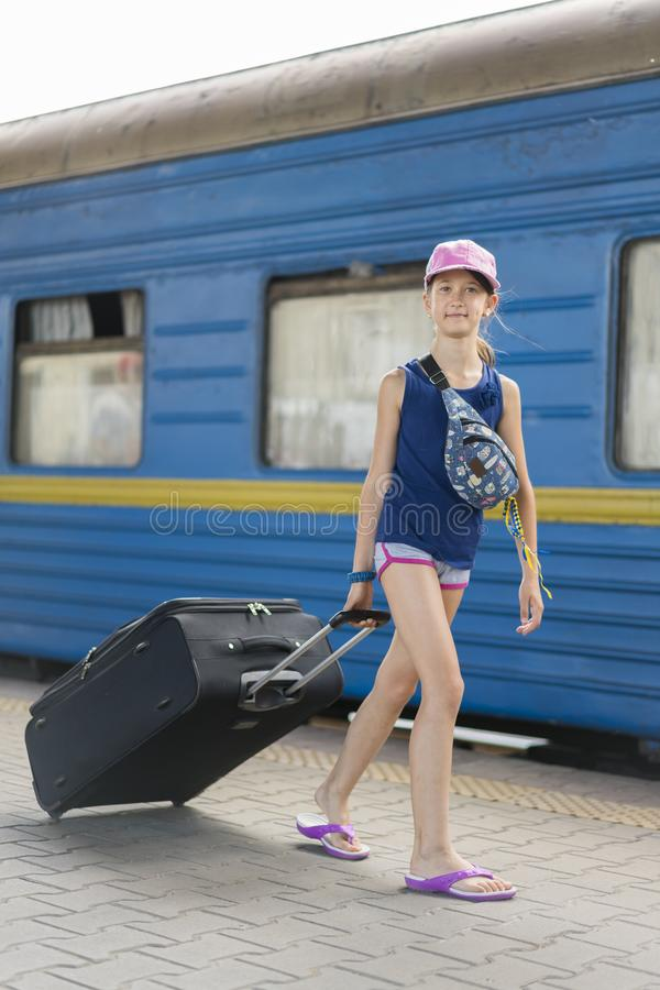 little sweet girl with a big suitcase on a deserted railway platform. girl pulling a large suitcase on the platform. vertical royalty free stock photography
