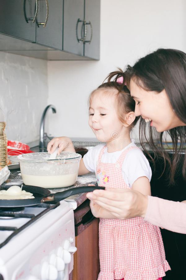 Little sweet girl and her mother fry pancakes at the traditional Russian holiday Carnival Maslenitsa Shrovetide stock images