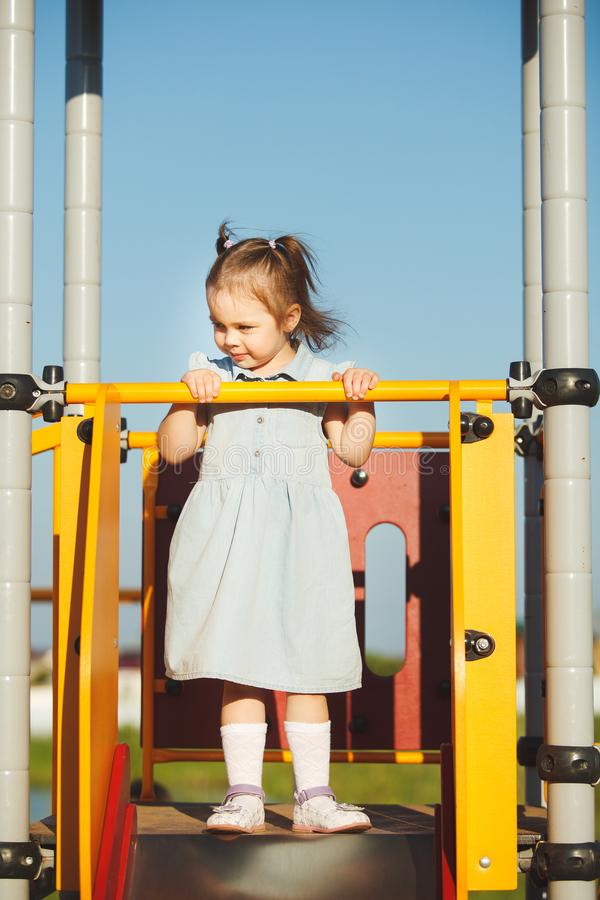 Little sweet girl on the hill in middle of playground. stock photos