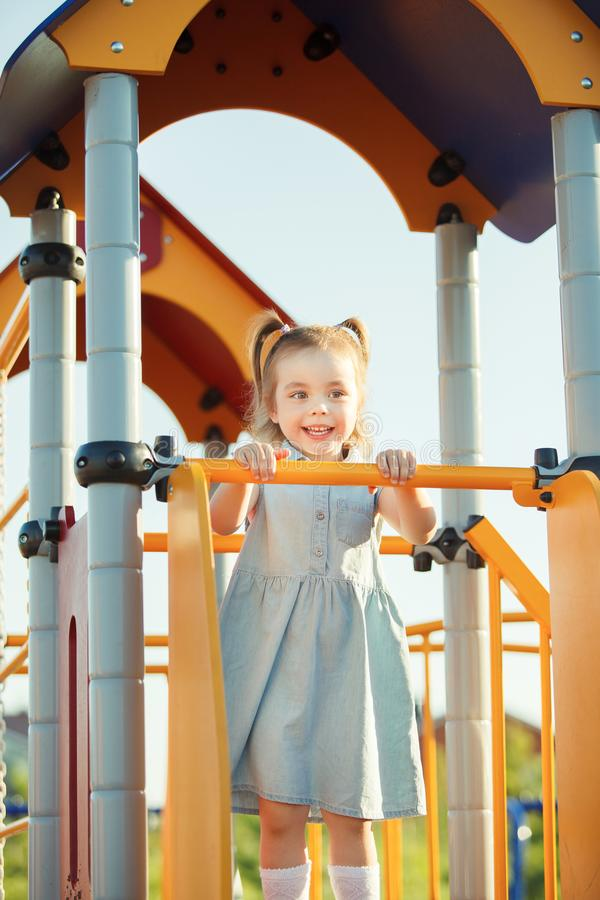 Little sweet happy girl on the hill in middle of playground. royalty free stock images