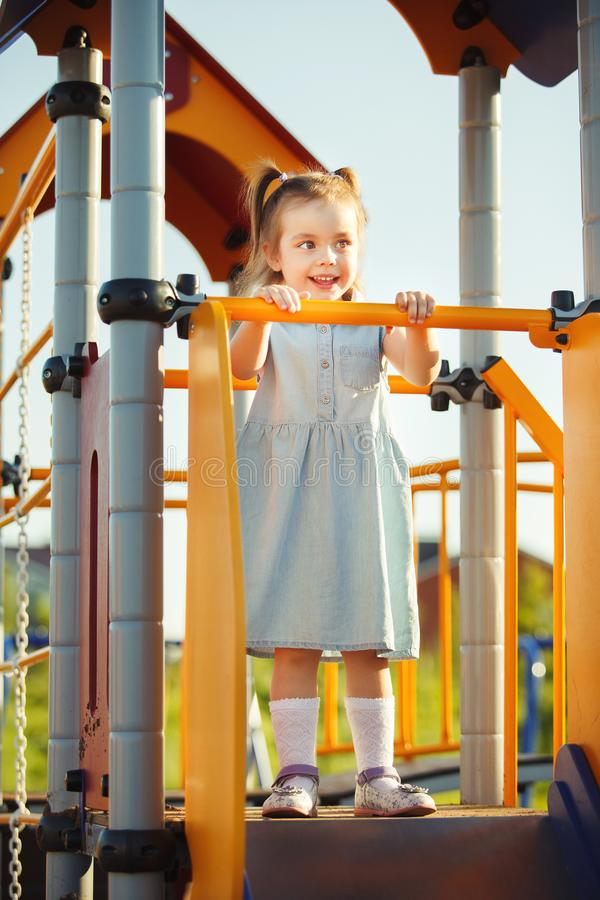 Little sweet happy girl on the hill in middle of playground. royalty free stock photos