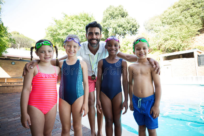 Little swimmers with trainer standing at poolside royalty free stock images