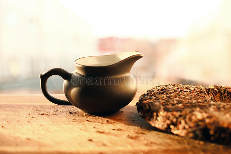 Little teapot with tea brick on table in the sunlight royalty free stock images