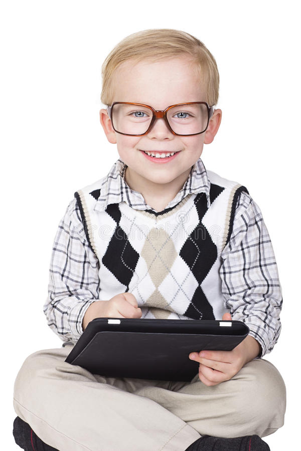 Little Technology Geek. A cute young technology wizard using a tablet computer. Isolated on a white background royalty free stock image