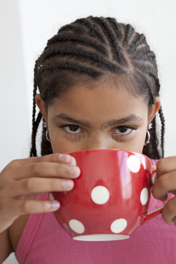 Little teenage girl is drinking a large cup of te royalty free stock images