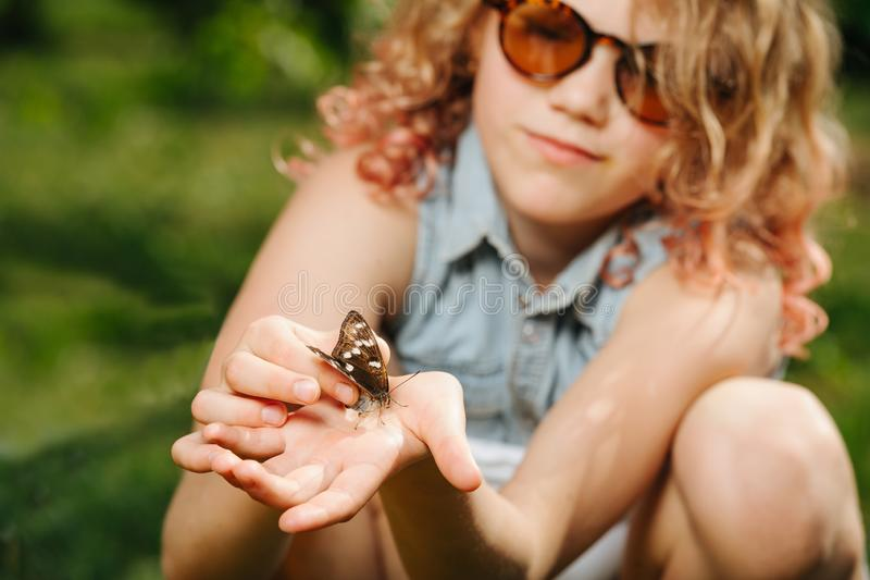 Little teenage girl holding butterfly in her hands. Little teenage girl with blond curly hair in sunglasses is gently holding butterfly in her hands royalty free stock photography