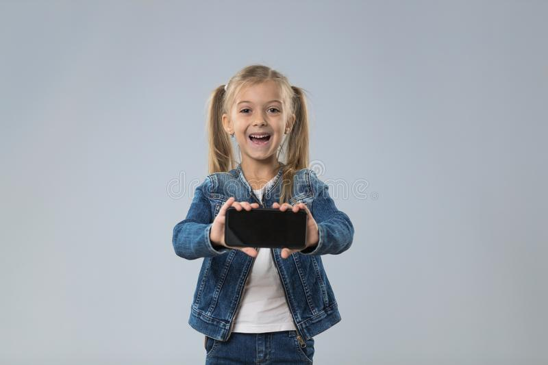 Little Teenage Girl Show Cell Smart Phone Screen With Empty Copy Space, Small Excited Happy Smiling Child. Isolated Over Gray Background stock image