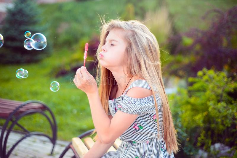 little teenage girl sitting on a bench blowing bubbles. Active lifestyle child royalty free stock photo