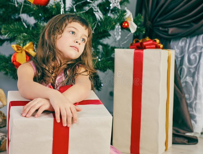 Little thoughtful girl dreams near a Christmas tree holding a big gift box. stock photography