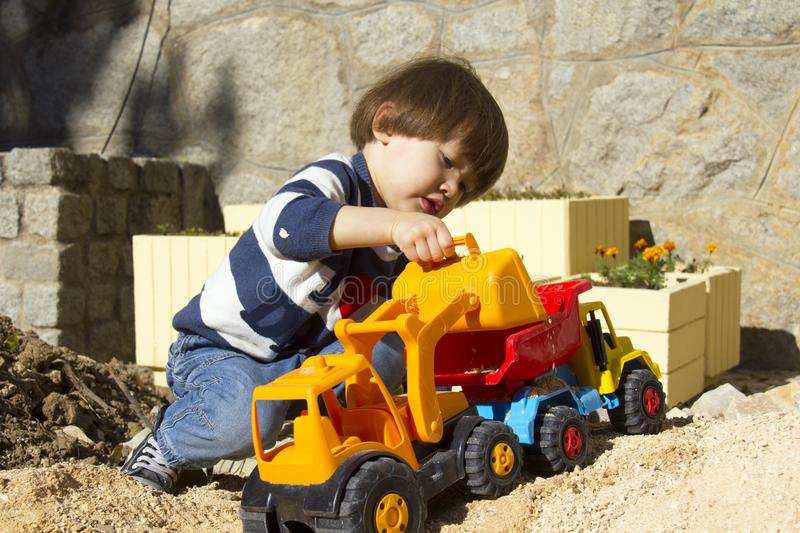 Little boy playing with toy digger and dumper truck. royalty free stock images