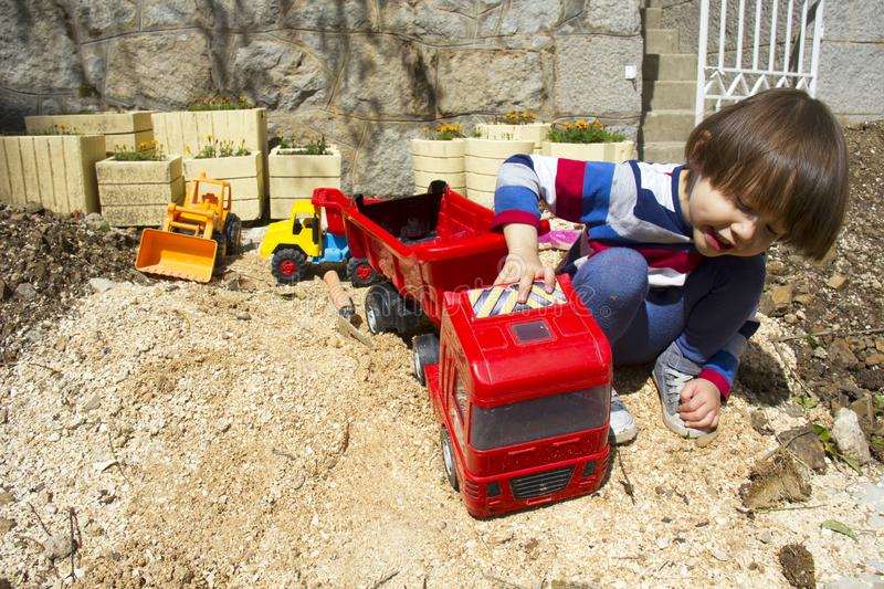 Little boy playing with toy digger and dumper truck. royalty free stock photography
