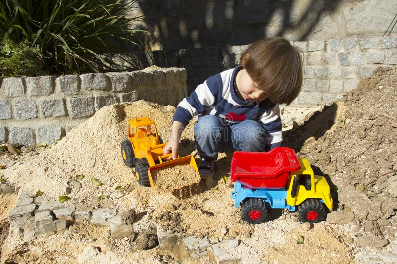 Little boy playing with toy digger and dumper truck. royalty free stock photo