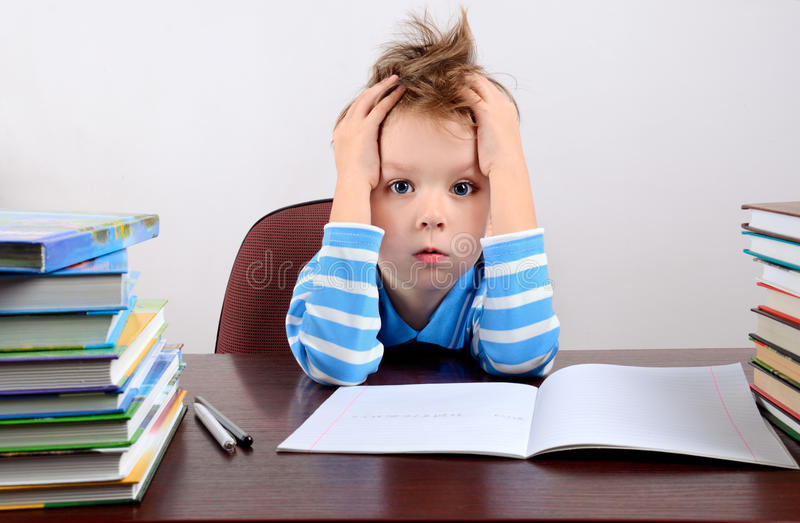 Little tired boy sitting at a desk and holding hands to head. Horizontal royalty free stock photography