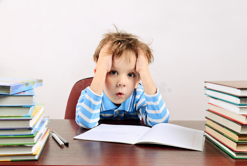 Little tired boy sitting at a desk. Horizontal stock images