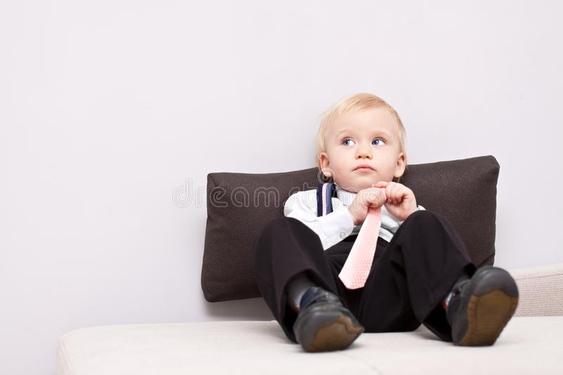 Download Little Tired Businessman Sitting On The Sofa Stock Photo - Image of person, cute: 13229278