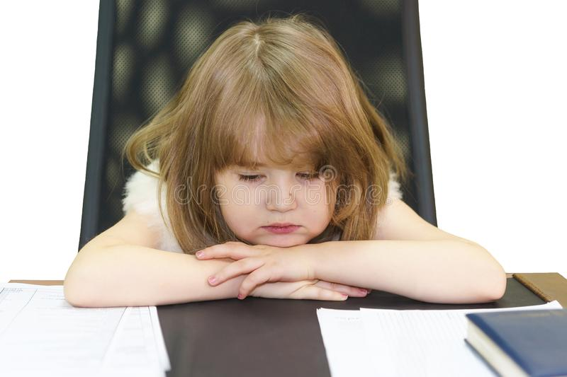 A little tired girl sitting on an adult workplace in the office stock image