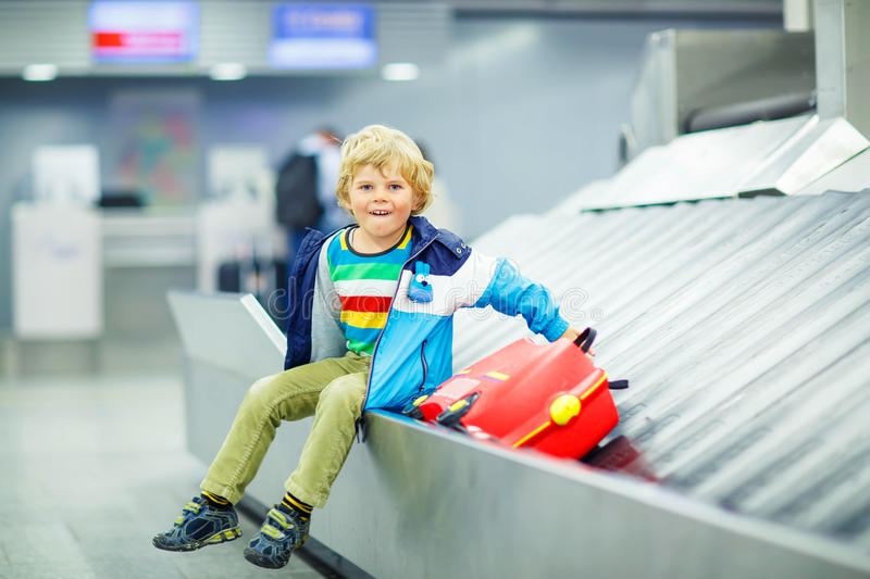 Little tired kid boy at the airport, traveling. Adorable little tired kid boy at the airport, traveling. Upset child waiting with kids suitcase on baggage royalty free stock photo