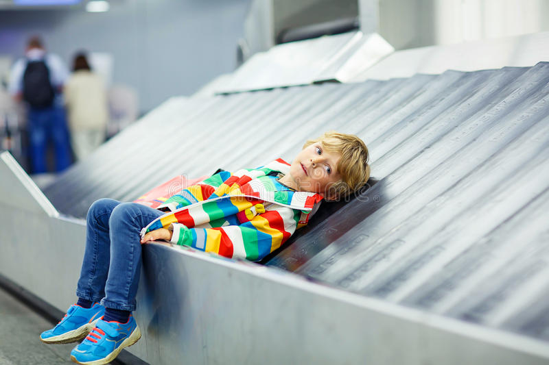 Little tired kid boy at the airport, traveling. Adoralbe little tired kid boy at the airport, traveling. Upset child waiting with kids suitcase on baggage royalty free stock photo