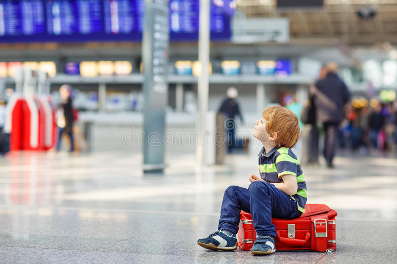 Little tired kid boy at the airport, traveling. Cute little tired kid boy sitting on suitcase at the airport, Sad child waiting with big suitcase. Canceled royalty free stock images