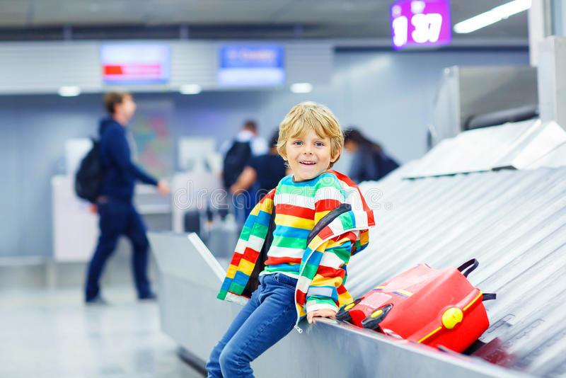 Little tired kid boy at the airport, traveling. Cute little tired kid boy at the airport, traveling. Smiling child waiting with kids suitcase on baggage carousel royalty free stock image