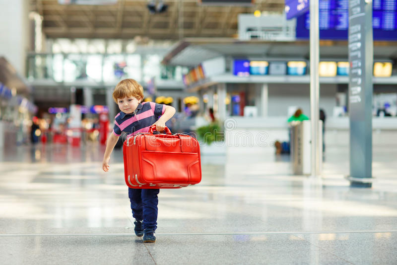Little tired kid boy at the airport, traveling. Cute little tired kid boy at the airport, traveling. Upset child waiting with big suitcase. Canceled flight due royalty free stock photo