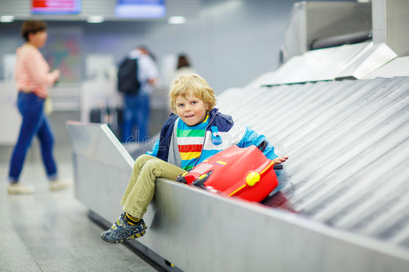 Little tired kid boy at the airport, traveling. Cute little tired kid boy at the airport, traveling. Upset child waiting with kids suitcase on baggage carousel stock image
