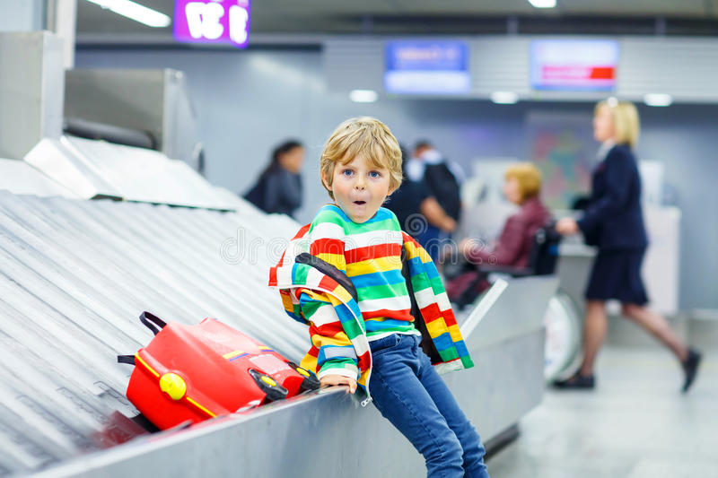 Little tired kid boy at the airport, traveling. Cute little tired kid boy at the airport, traveling. Upset child waiting with kids suitcase on baggage carousel royalty free stock photography