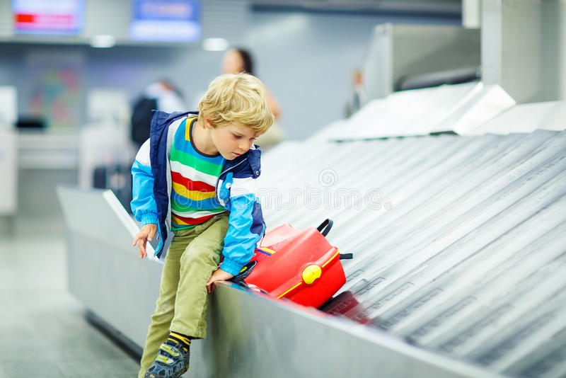 Little tired kid boy at the airport, traveling. Cute little tired kid boy at the airport, traveling. Upset child waiting with kids suitcase on baggage carousel stock photography